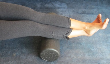Foam Roller under ankles to support alignment exercises; back pain; hip pain; leg pain; pain relief